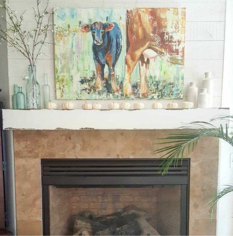 fireplace with cow painting and white pumpkins