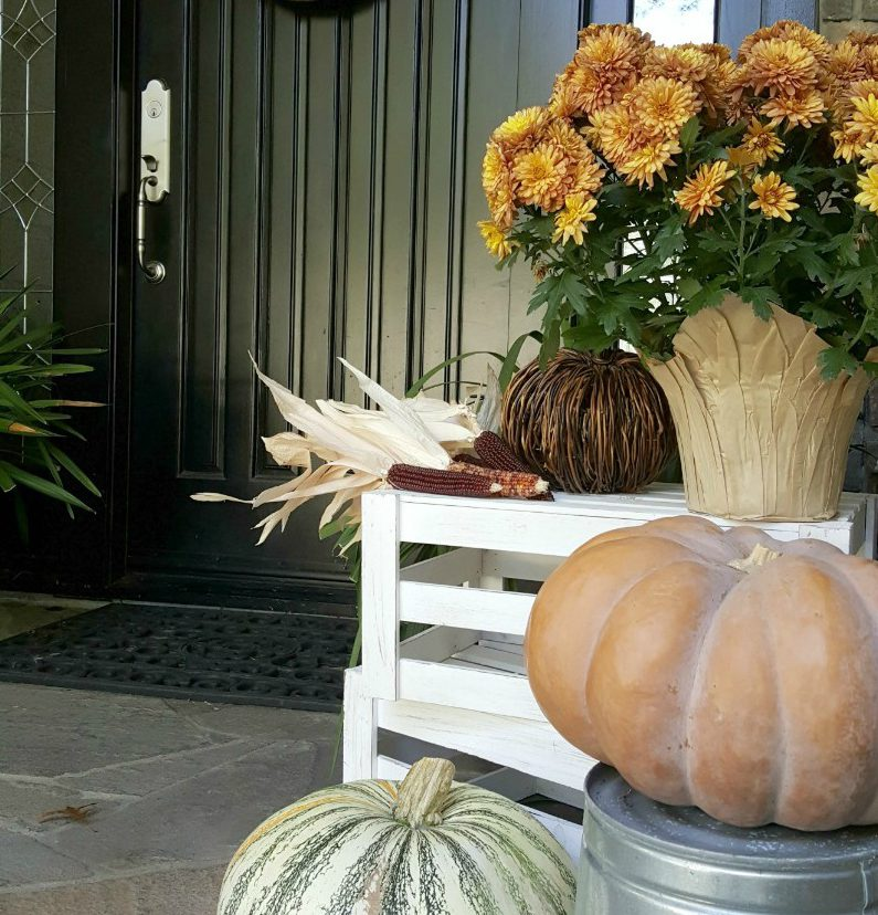 fall front door with pumpkins and mums