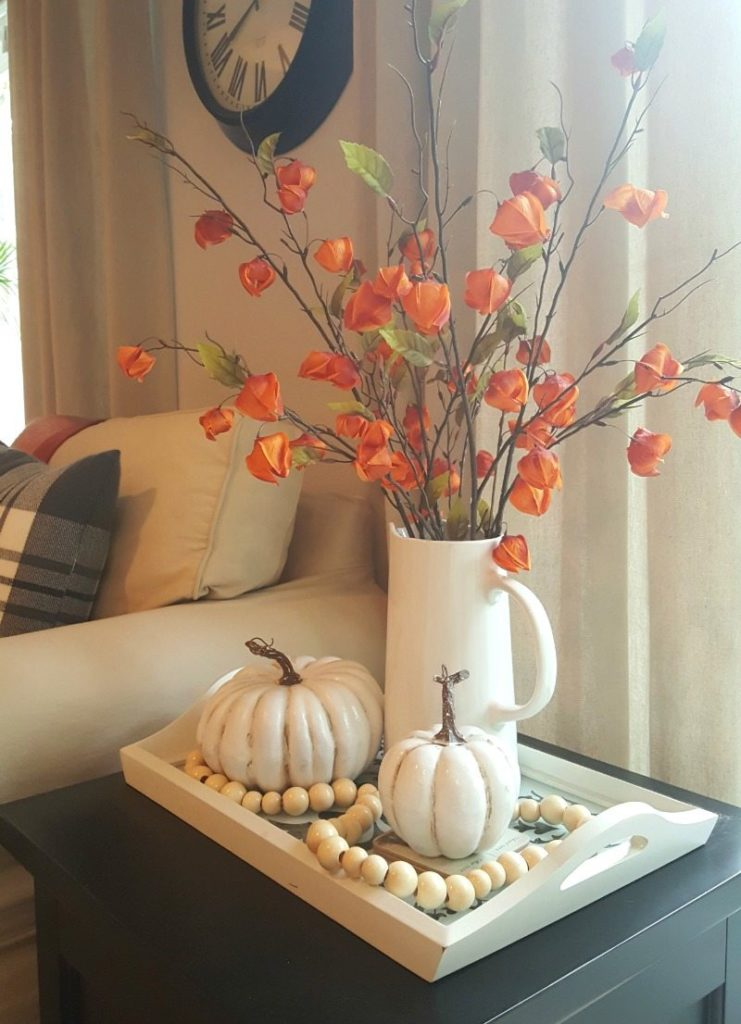 fall vignette with orange florals and pumpkins