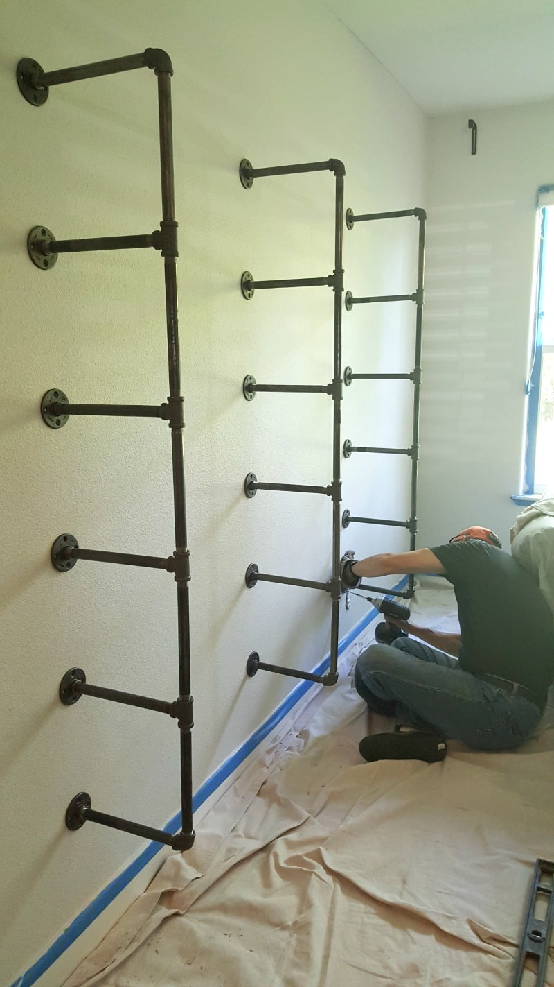 Installation process attaching support brackets to wall for DIY Pipe shelf project