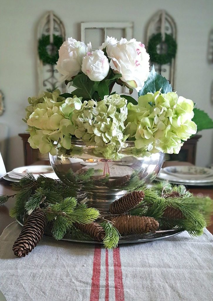 Dining room floral center piece with pine cones, evergreen in an antique punch bowl for an inspired Christmas decor theme