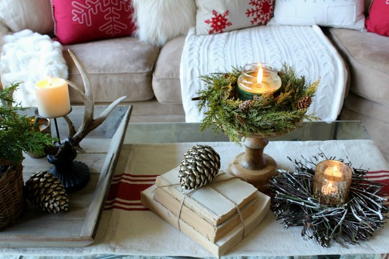 Use rustic elements to create a cozy traditional appeal to your holiday decor with evergreen, pine cones, and antlers