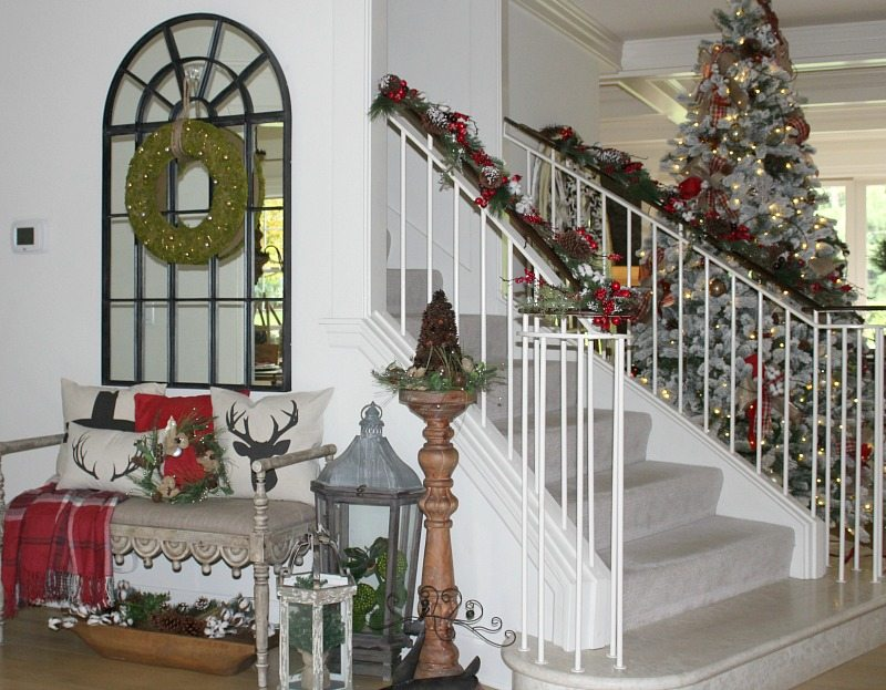 avoid holiday stress with Christmas Entryway decorated with flocked tree, mirror and bench with holiday pillows