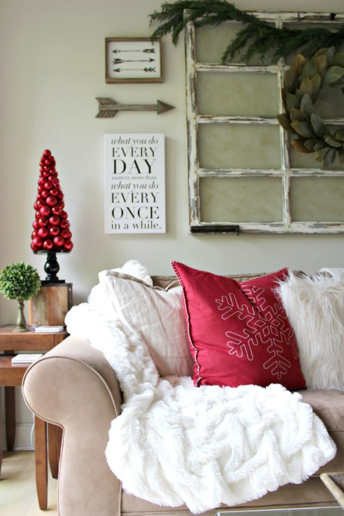 Holiday decorating with rustic farmhouse details add warmth to traditional family room decor with red, white and green accents