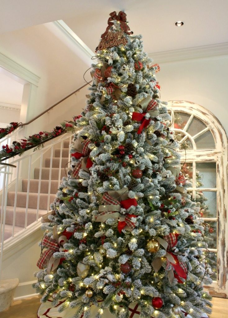 Flocked King of Christmas Tree is gorgeously decorated with ribbon and traditional elements