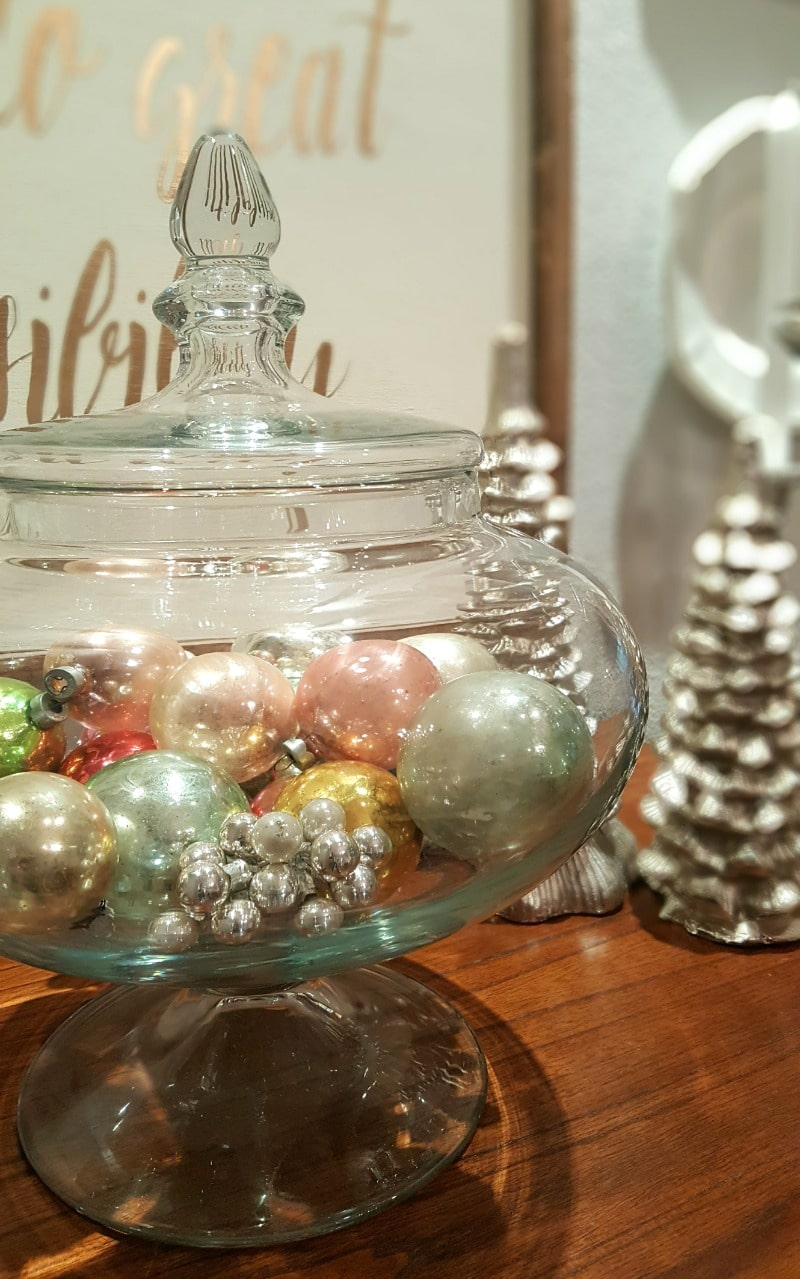 vintage ornaments decorate table top in glass canister