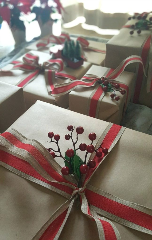 brown paper packages with holly and red ribbon close up