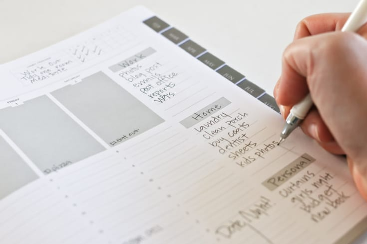 hand writing down goals in journal with spaces for daily and weekly goals and reminders