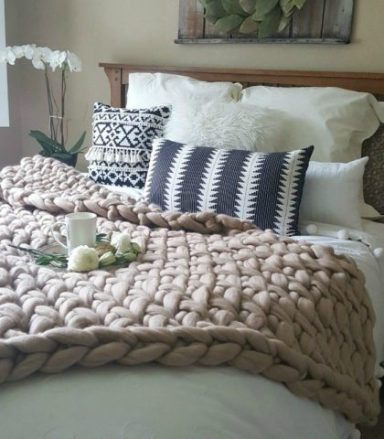 farmhouse style bed covered in luxurious handknit wool blanket