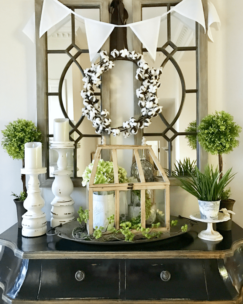 black console with greenery entryway decorating