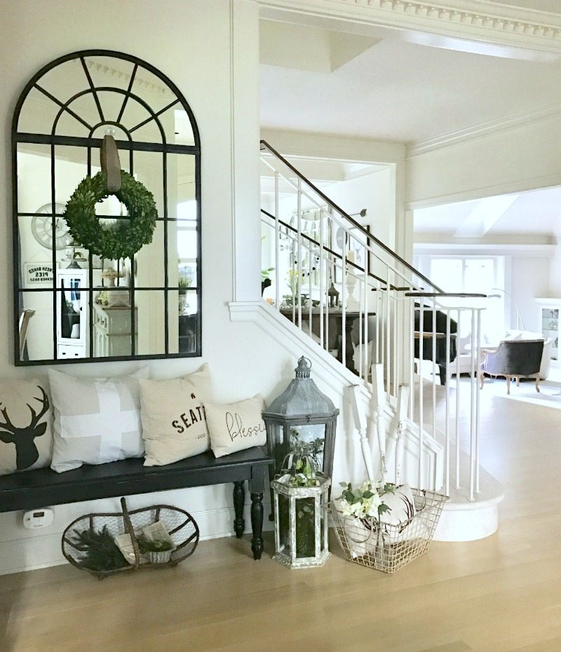 front entryway decor with bench and window mirror