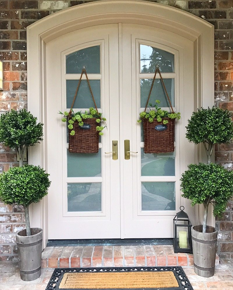 front door front porch with greenery and hanging door baskets
