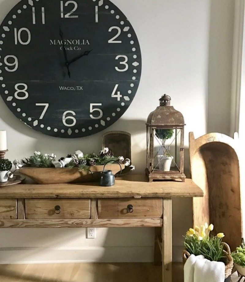 oversized clock above farmhouse table with dough bowl