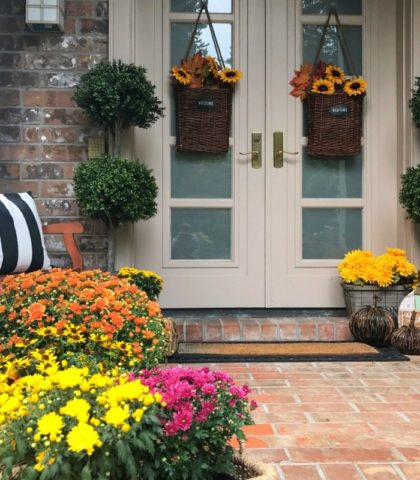 fall front door decorated with mums baskets of flowers and pillows