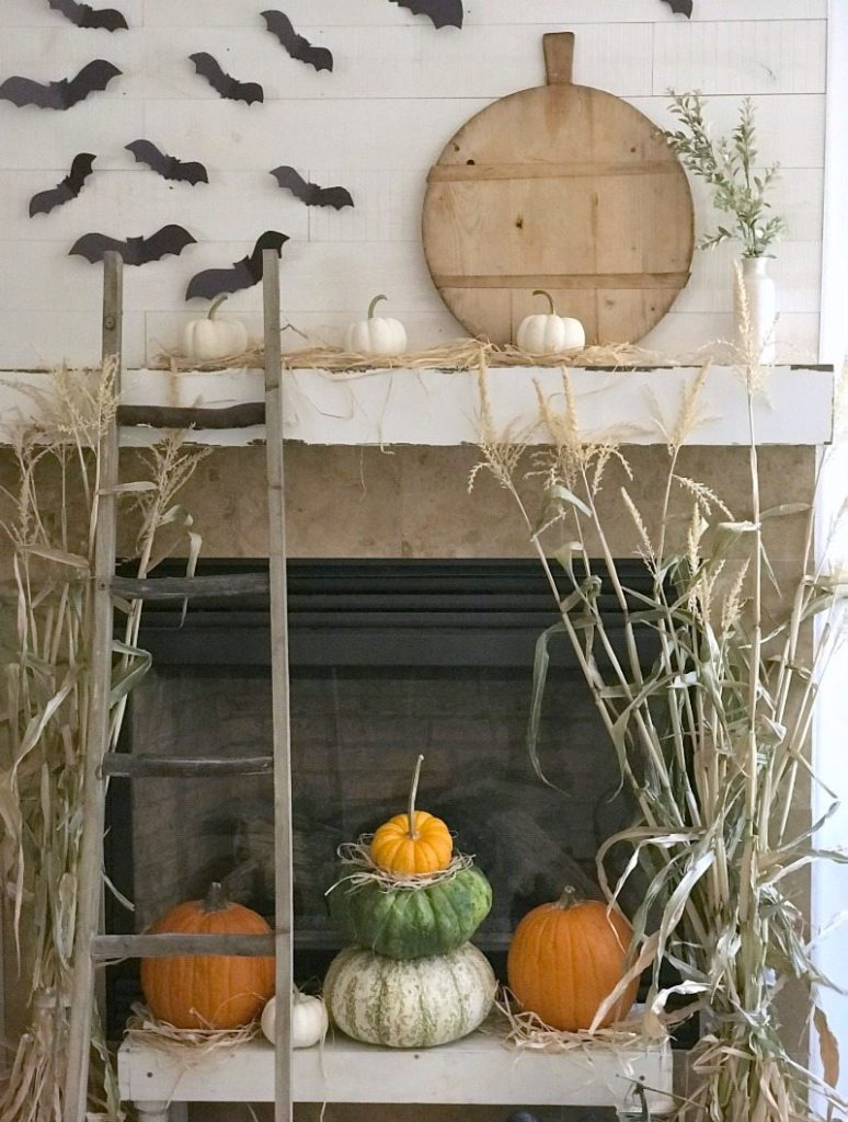 Simple acitvivity paper bats over fireplace with pumpkins and ladder