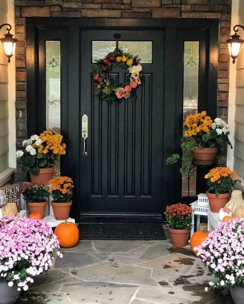 black front door with orange and white flowers