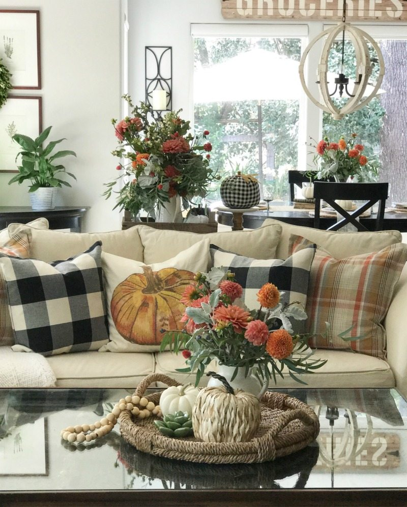 pumpkin and plaid pillows with flowers in living room