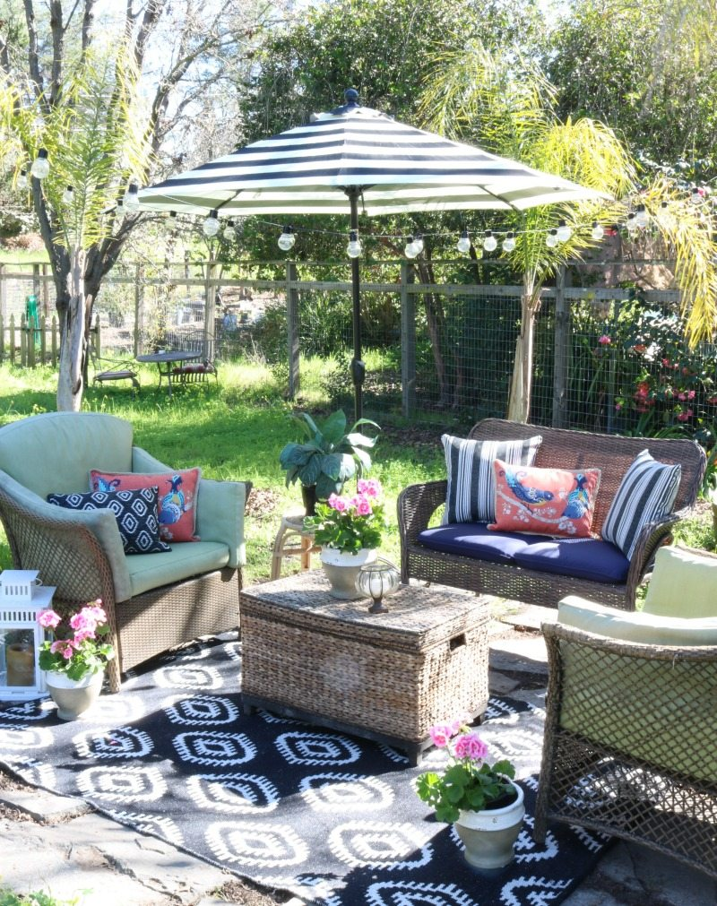 outdoor seating area with umbrella and rug