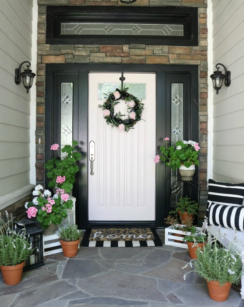 pink painted front door and striped accents and flowers