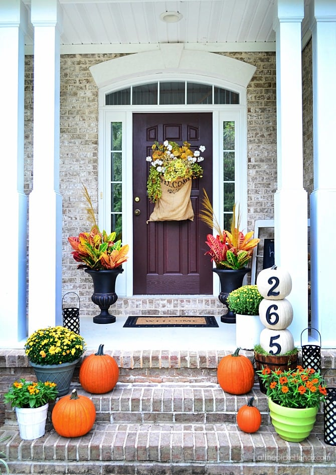 hanging door basket with flowers and pumpkins on front porch