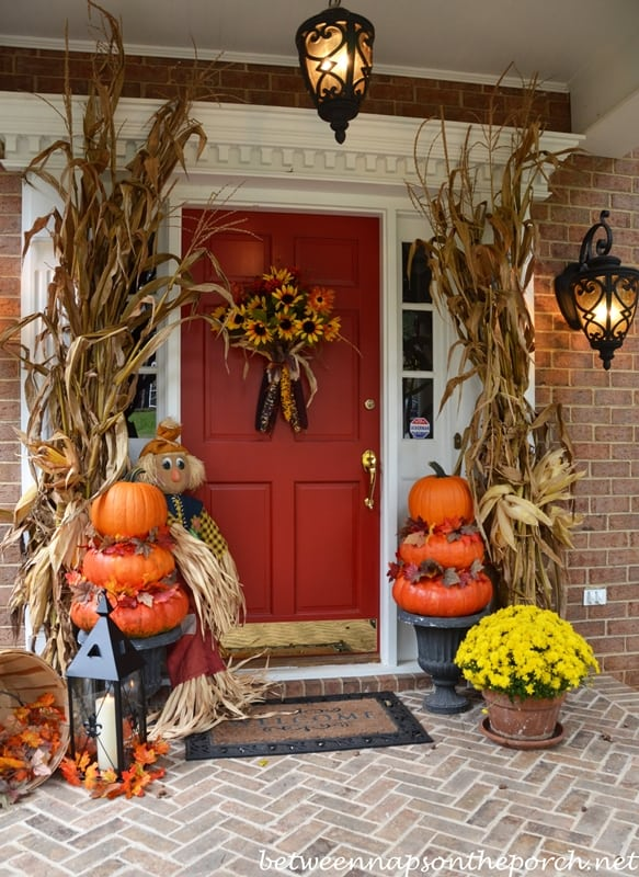 red front door withe orange pumpkins and corn husks