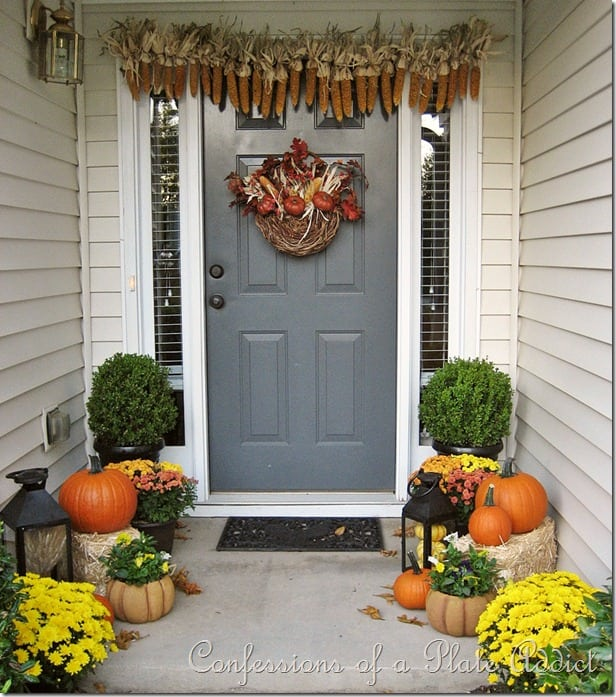 corn husk garland and hay bails with orange pumpkins