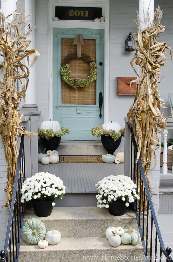 blue front door with white mums and blue and white pumpkins