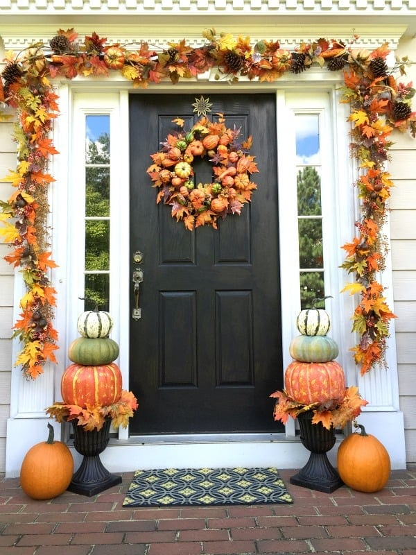 black front door with pumpkin and leaf garland and wreath