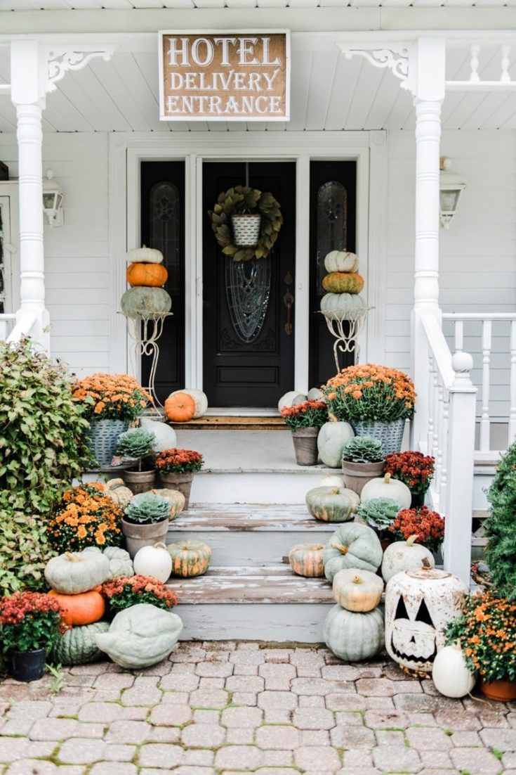 farmhouse fall front porch with pumpkins and mums