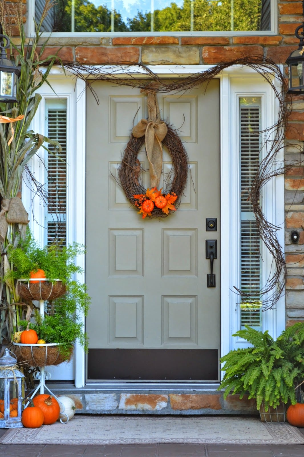 grey front door with orange pumpkins and wreath