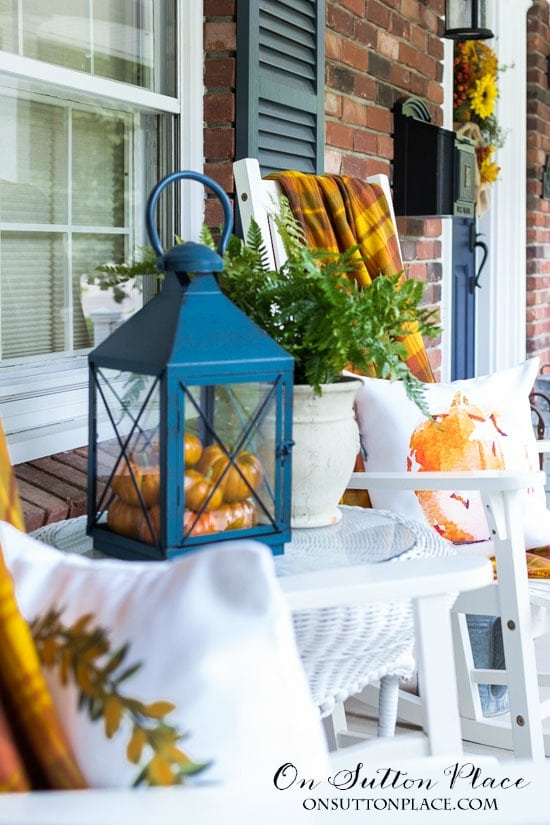 black lanterns with mini pumpkins and orange accents