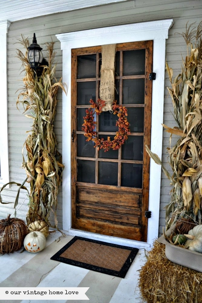corn husks at wood front door with wicker pumpkins