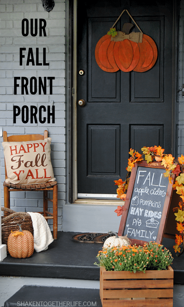 chalkboard sign with black front door and orange pumpkin sign
