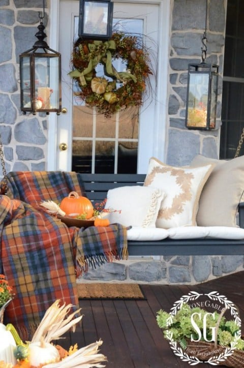 front porch swing with hanging lanterns and plaid throw