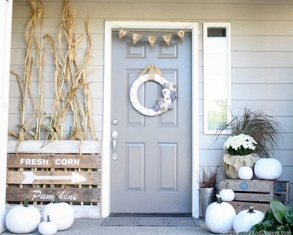 grey front door with white pumpkins and corn husks