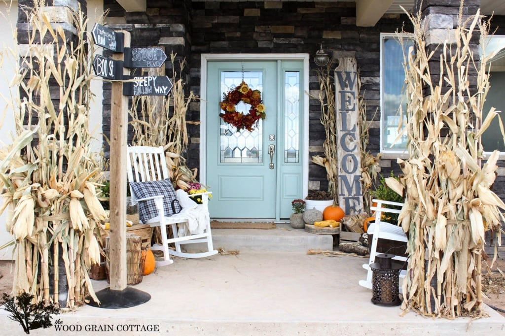 blue front door with white rocking chair and corn husks