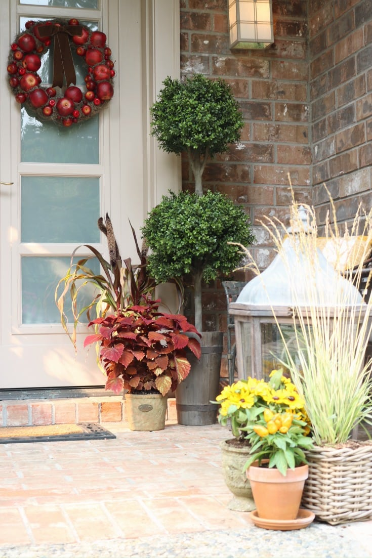 fall front door porch with greenery and lanterns