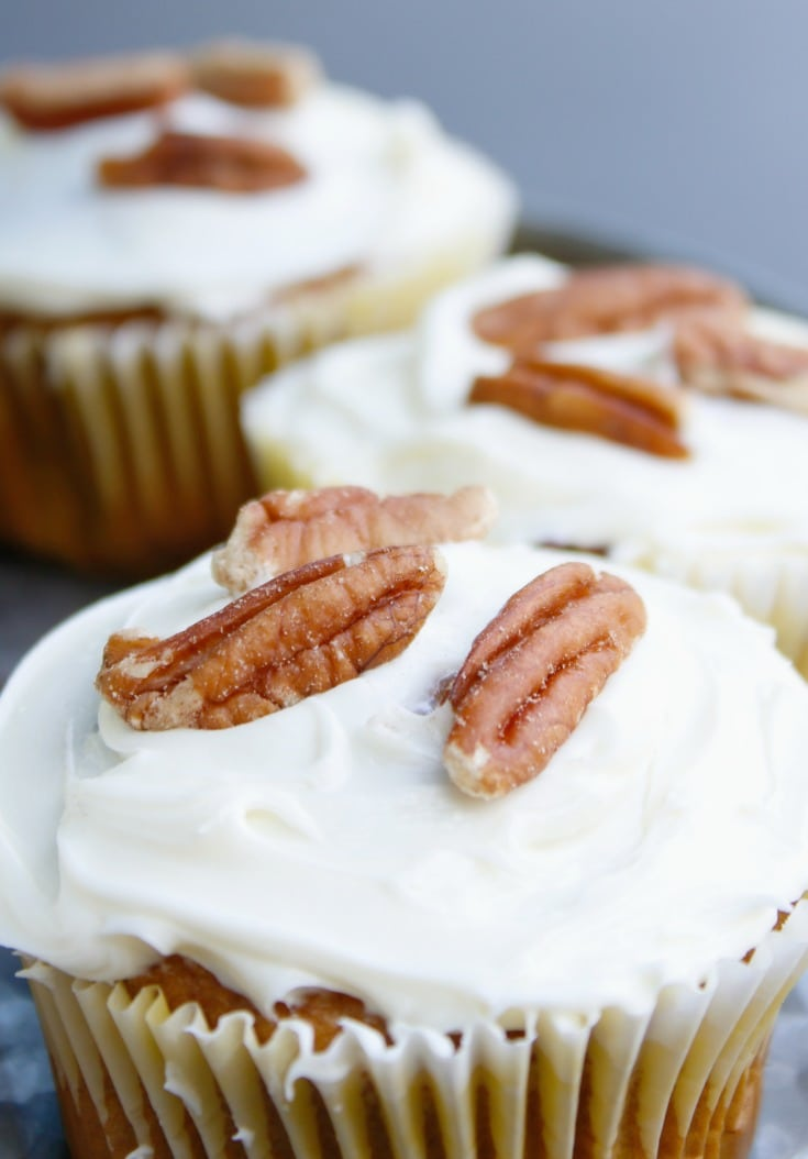 close up pumpkin spice cupcakes with cream cheese frosting and pecans