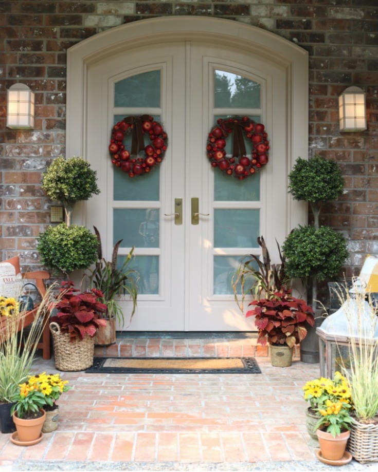 Festive fall home porch with mums and apple wreaths