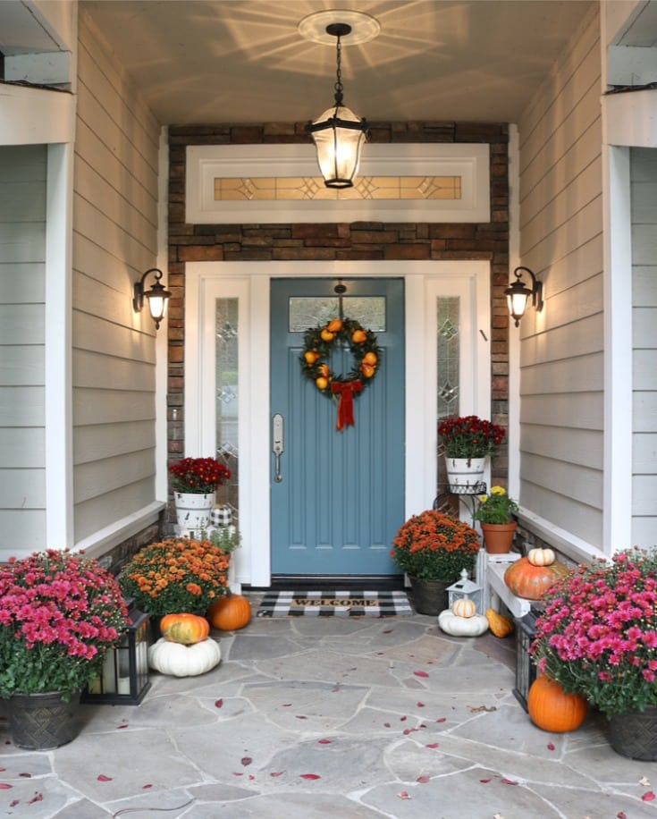 slate blue front door with bright colored mums and pumpkins for fall