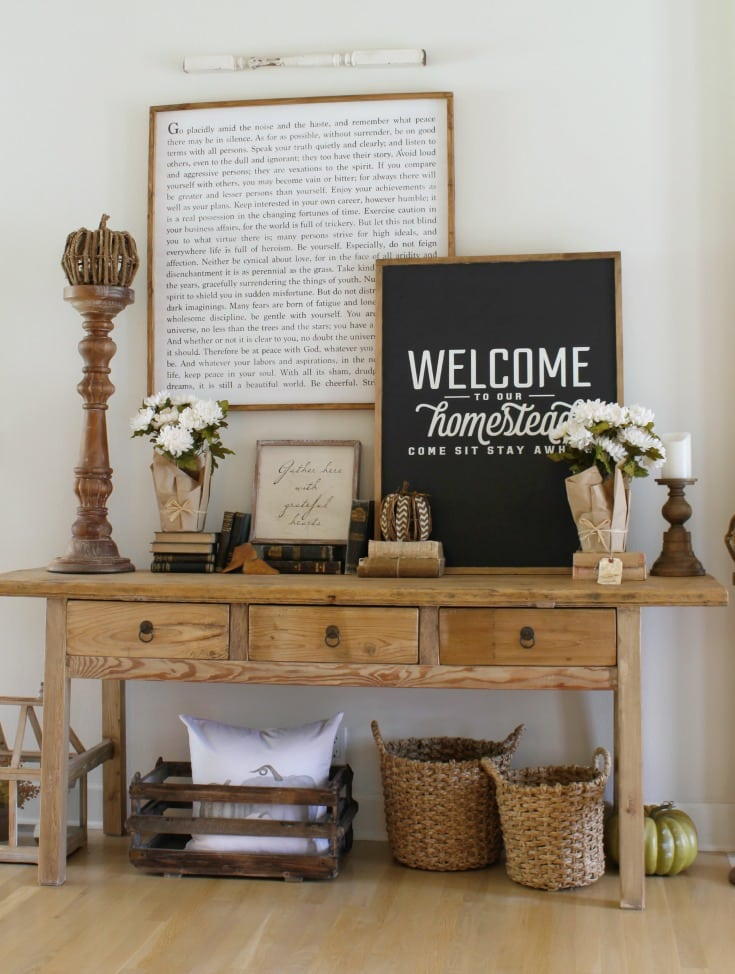 fall farmhouse table vignette with pillows and baskets and signs