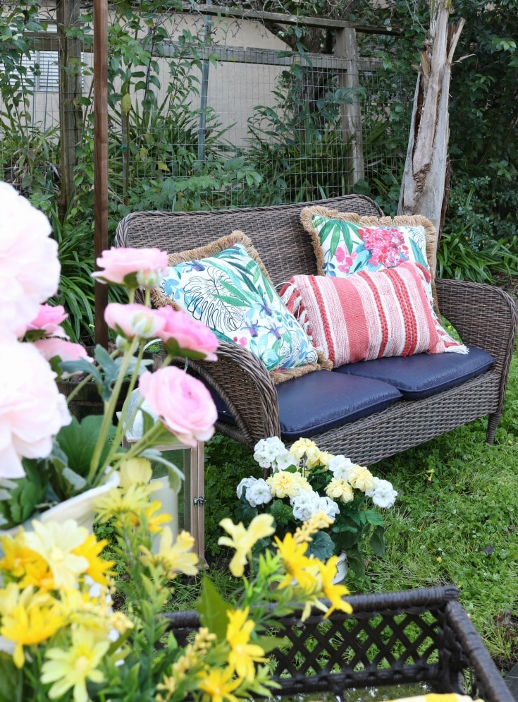 wicker bench with spring pillows and flowers