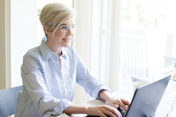 woman is happy working on laptop because she understands winning Instagram strategies for success.
