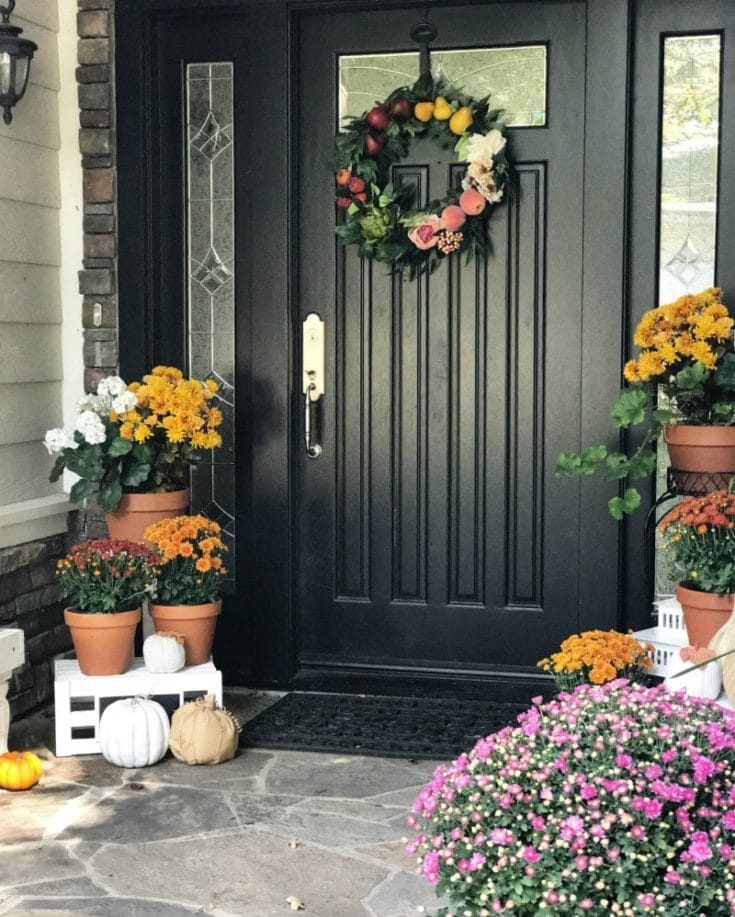 Black front door with fall wreath and fall mums and pumpkins