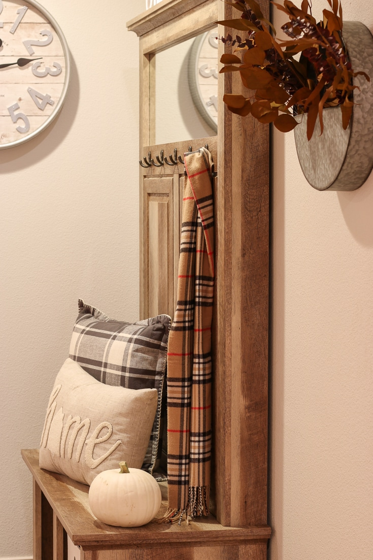Stylish Entryway Bench and Storage Unit decorated for fall with plaid pillows and pumpkins