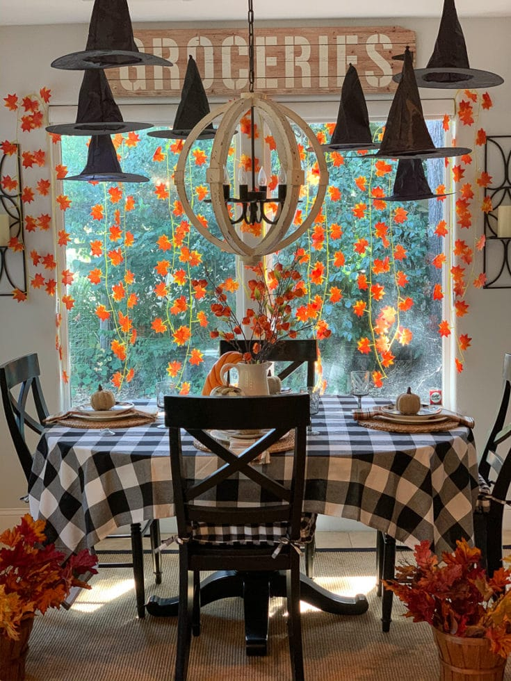 Whimsical and festive Halloween decor comes to life with floating witches hats and garlands of autumn leaves