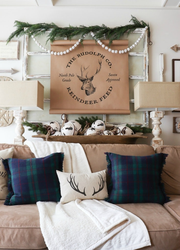 farmhouse reindeer sign with greenery and blue and green plaid pillows from Better Homes and Gardens at Walmart