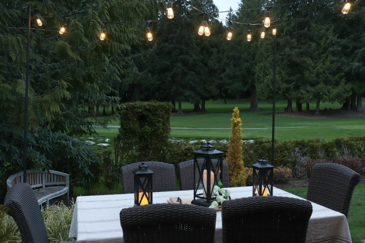 outdoor dining table with string lights overhead