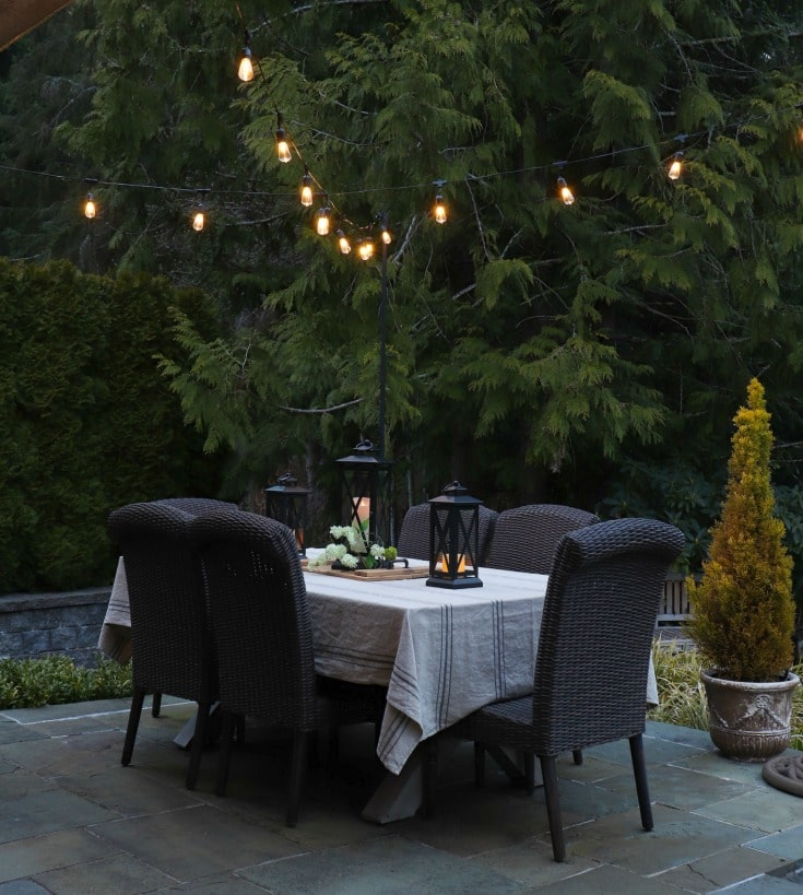 outdoor dining table with overhead string lights adds the perfect amount of mood lighting