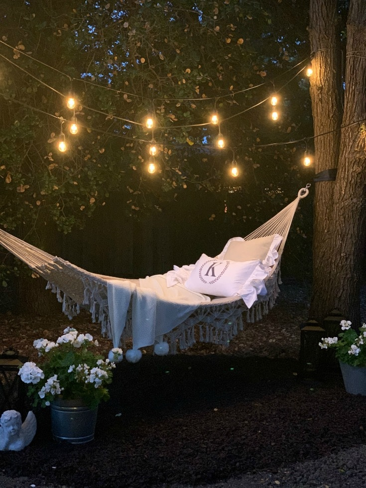 hammock with string lights and pom pom throw at night